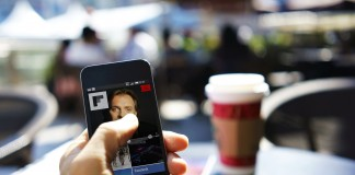 Close-up view of a hand using mobile news app Flipboard in a cafe