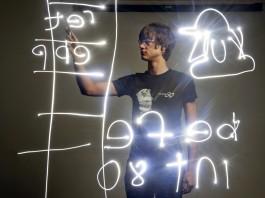 Un jeune homme derrière un tableau transparent avec des chiffres et un tracé lumineux (AP Photo/Tribune Review)