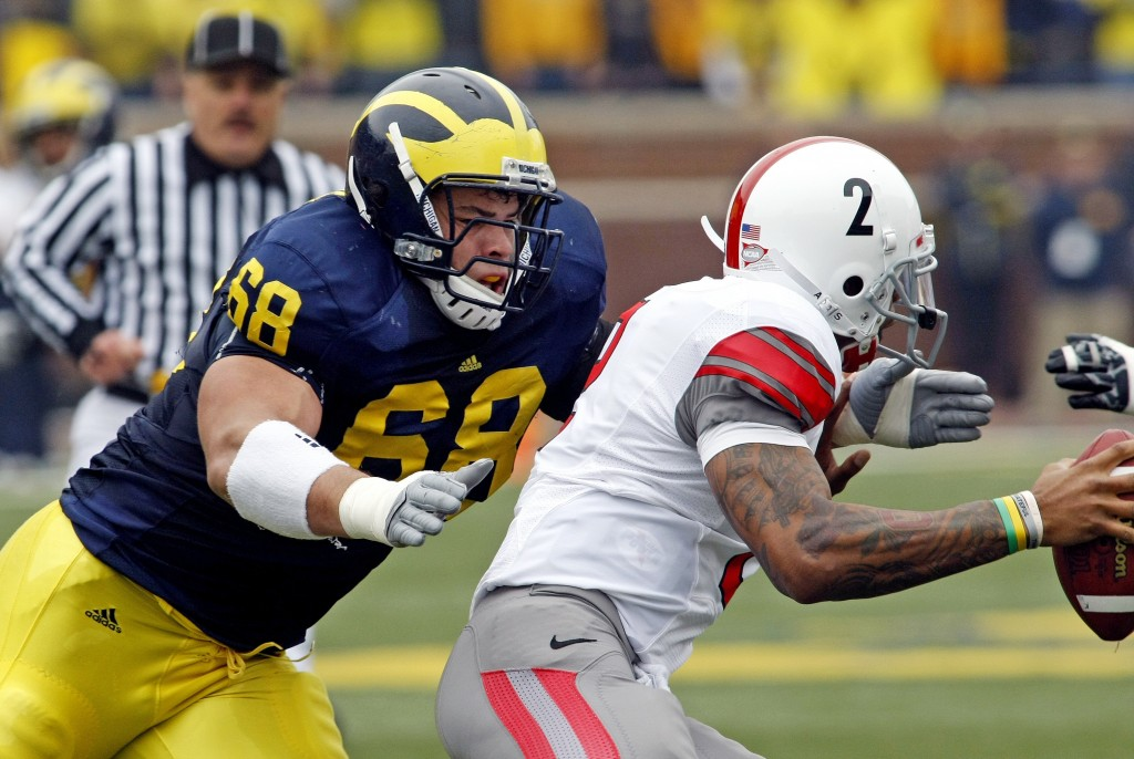 """The football player in blue and yellow """"blindsides"""" the quarterback in white. (AP Images)"""