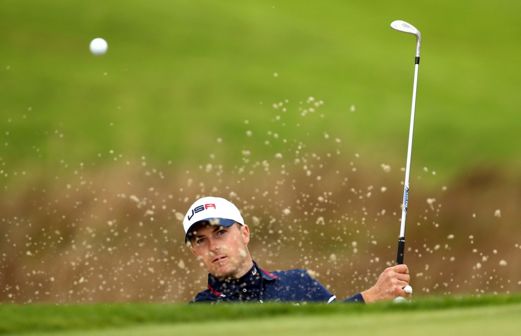 Golfer hitting ball in sand trap (AP Images)