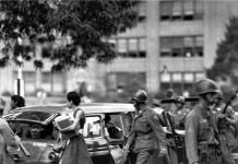 Photo d'époque montrant des soldats marchant aux côtés de jeunes, avec une voiture en arrière-plan d'où sort une jeune noire (AP Images)