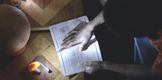 Hands holding homework lit by Soccket (Courtesy Uncharted Play)