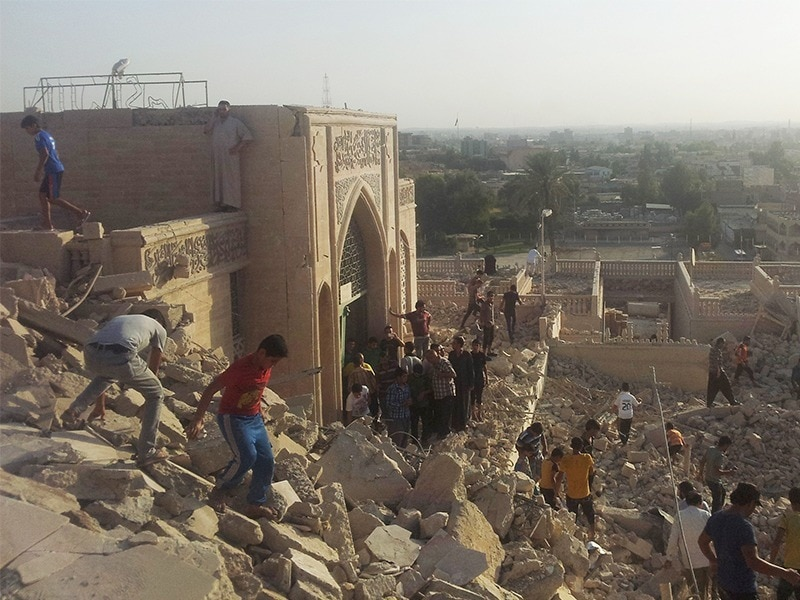 Residents try to find artifacts at the Mosque of the Prophet Younis in Mosul, Iraq after being destroyed by ISIL