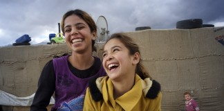 Two Syrian girls laugh together in a refugee camp