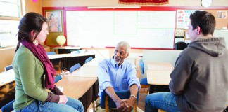 Three people seated and talking in classroom (Blend Images/Inmagine)