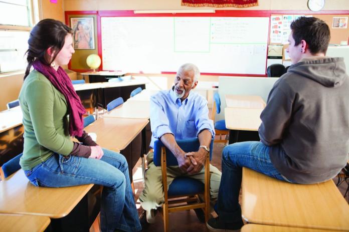 سه نفر در یک کلاس درسی نشسته اند و با هم صحبت می کنند (Blend Images/Inmagine)