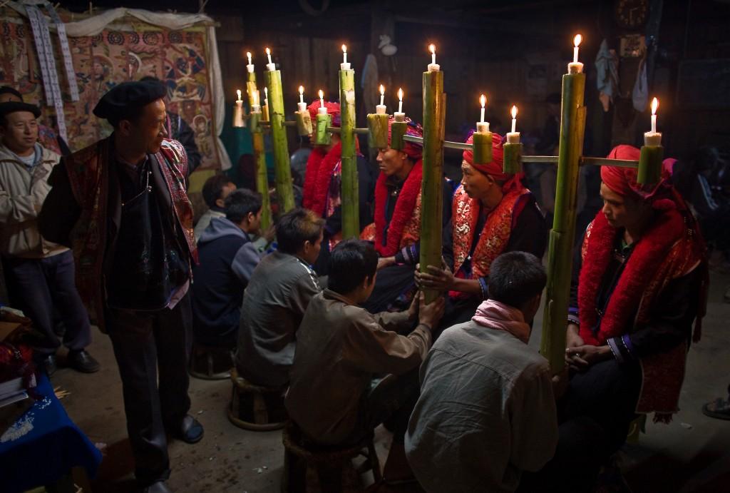 Des jeunes gens assis, portant un turban rouge, des garçons sur des tabourets, tenant des cierges, et deux hommes plus âgés debout (Crédit photo : Traditional Arts and Ethnology Centre, Kees Sprengers)