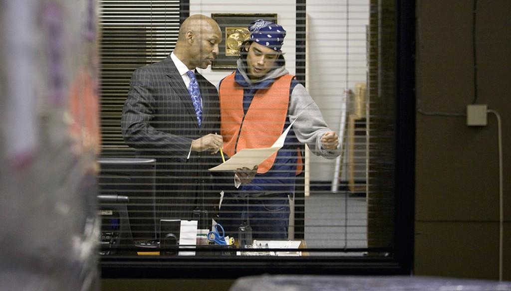 Two people talking inside office (Thinkstock)