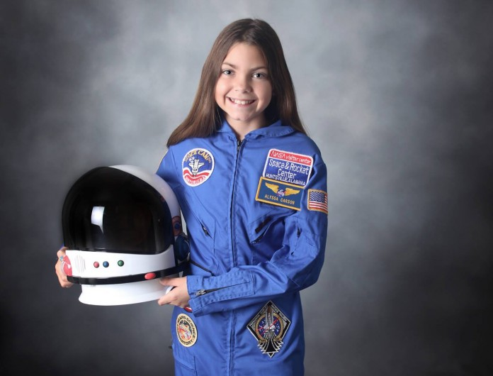 Alyssa Carson in astronaut suit, with helmet in hand (Facebook)