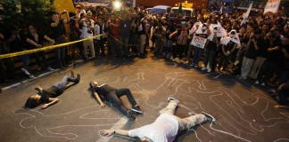 People portraying corpses surrounded by crowd (AP Images)