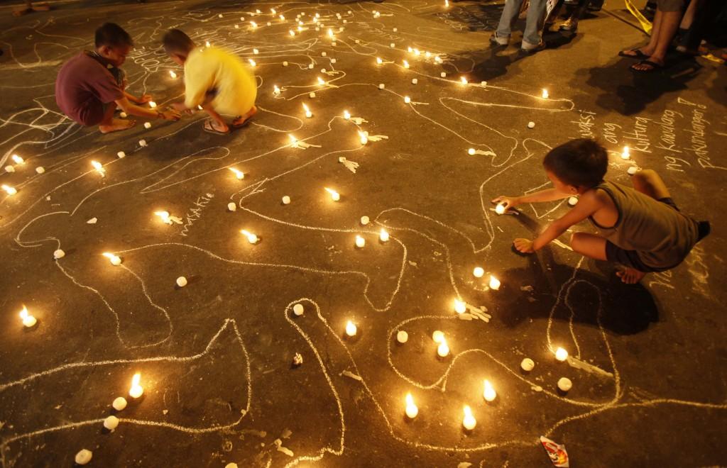 Crianças adicionam luzes para delinear desenhos feitos no chão (AP Images)