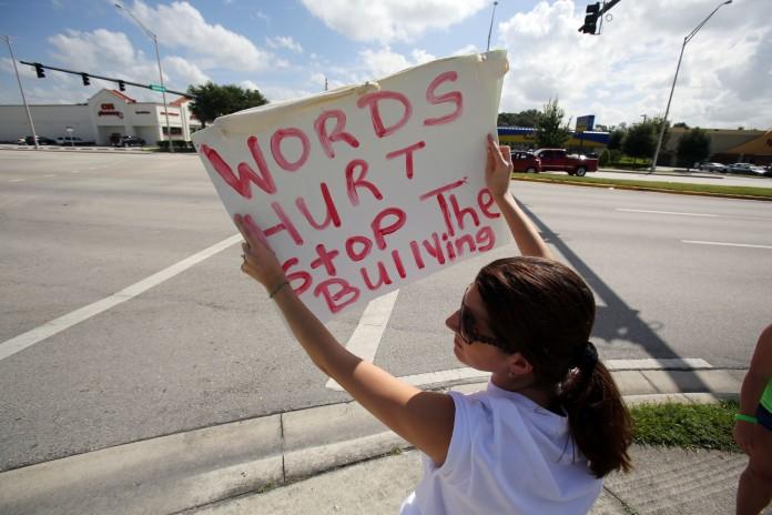 Estudiante con pancarta contra el hostigamiento (AP Images)