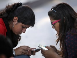 Indian girls using mobile phones (AP Images)