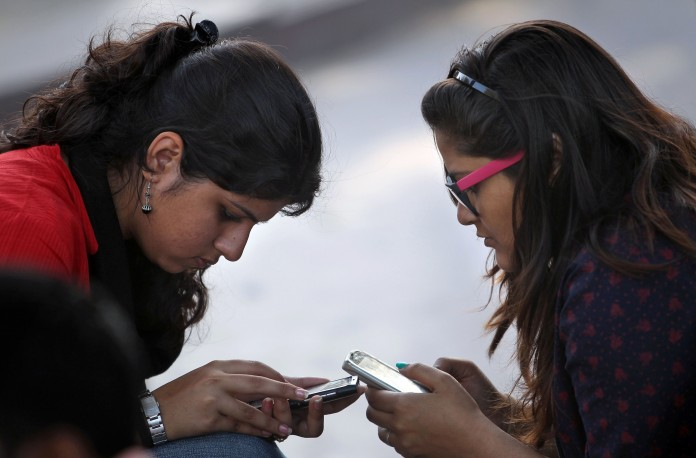 Indian girls using mobile phones (AP Images)