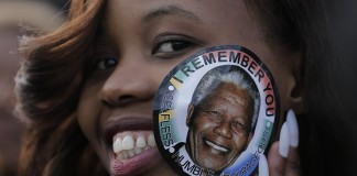African woman with Mandela sticker. Fellowship for Young African Leaders honors Mandela (AP Images)