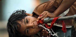 Girl drinking water from pipe (AP Images)
