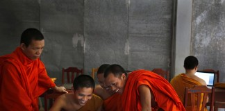 Monks in orange robes looking at computer screen (AP Images)