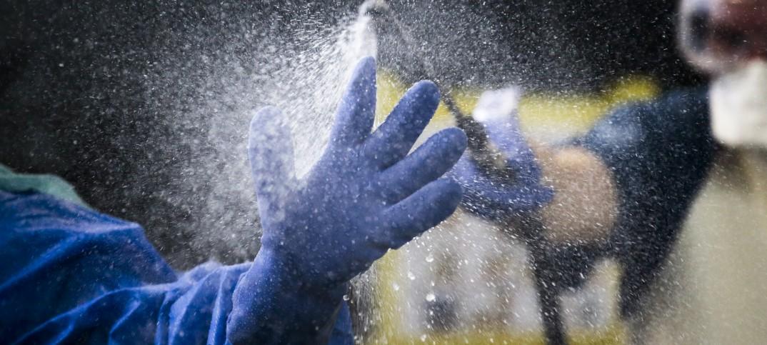 Agua cae sobre guantes en un ejercicio sobre el ébola (AP Images)