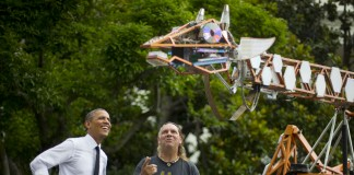 President Obama and another man looking at a makers' creation (AP Images)