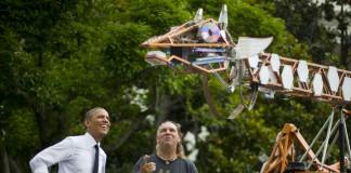 El presidente Obama y otras personas miran la creación de un fabricante (AP Images).