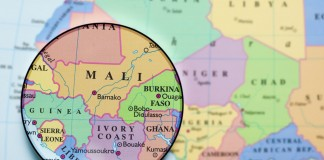 Magnifying glass laid on map of West Africa (Thinkstock)