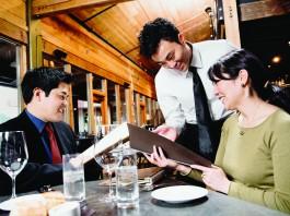 Homem e mulher sentados à mesa fazem pedidos de pratos ao garçom (Ned Frisk/Blend Images)