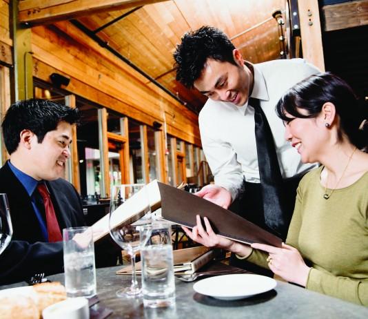 Un hombre y una mujer sentados a la mesa ordenando su comida a un camarero (Ned Frisk/Blend Images)