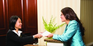 A woman speaking with the receptionist at a hotel (Thinkstock)