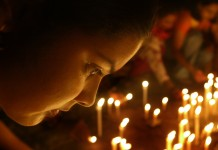 Woman looking at many lit candles during vigil (© AP Images)