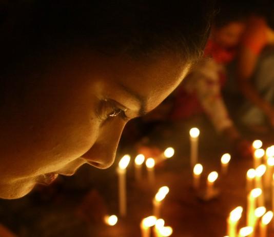 Une femme, le visage penché sur beaucoup de bougies (© AP Images)