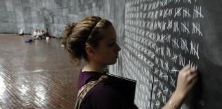 فتاة تكتب على سبورة (© AP Images)