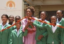 Oprah Winfrey coupant un ruban devant une école, entourée d'enfants.