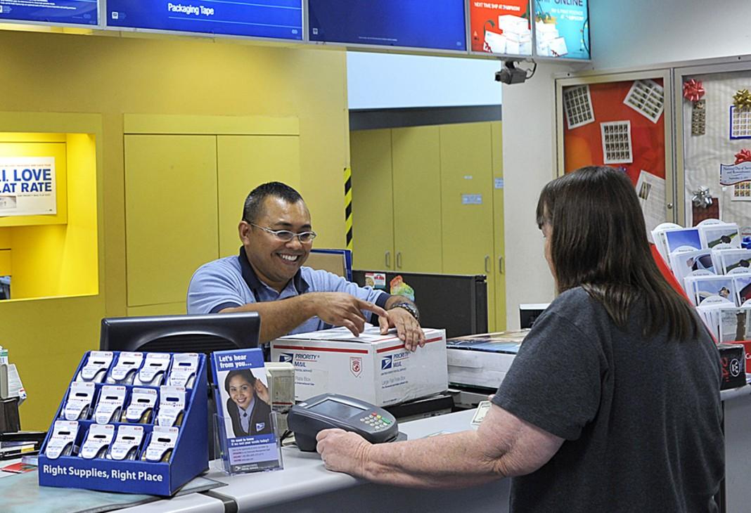 Une femme dans un bureau de poste, un employé derrière le comptoir