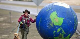 مردی با یک سگ و یک کره زمین بزرگ (© عکس از آسوشیتدپرس)
