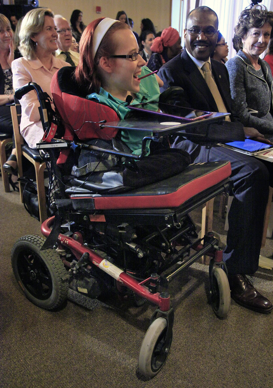 """جوآن اروبوردان، اهل ناحیۀ کورک، ایرلند، در کنفرانس اتحادیۀ ارتباطات دور، وابسته به سازمان ملل متحد حضور یافته است. او یکی از هفت تنی است که در دنیا دچار بیماری مادر زادی """"توتال امیلیا"""" هستند. این بیماری سبب می شود که افراد بدون دست و پا  متولد شوند."""