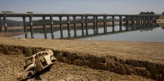 Le châssis d'une voiture gisant sur un sol aride près d'un pont (© AP Images)
