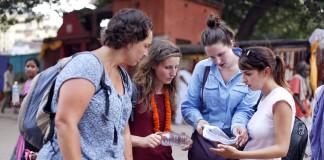 Cuatro personas hablan sobre la dirección a tomar mientras miran un mapa (© AP Images)