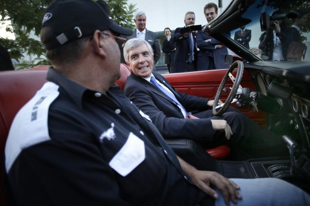 Deux personnes dans une voiture décapotable, avec d'autres personnes autour (© AP Images)