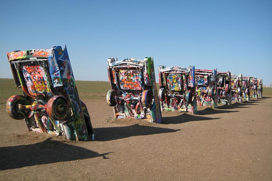 مجسمه ای ساخته شده از اتومبیلهایی که رنگهای درخشان دارند و در شن دفن شده اند. به لطف ریچی دایستر هفت