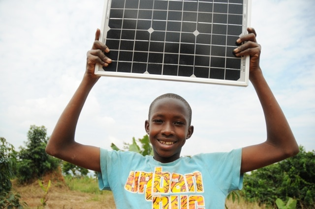 Young boy holding solar panel (Courtesy Fenix International)