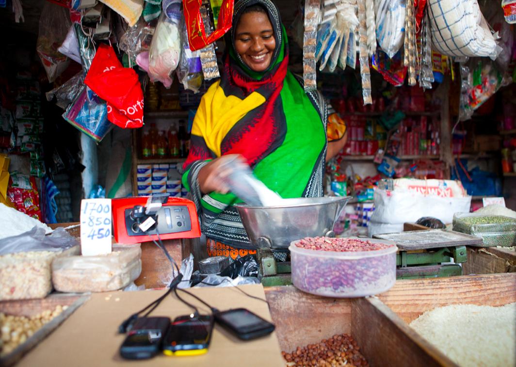 Woman standing at market kiosk (Courtesy Fenix International)