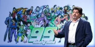 Al-Mutawa em pé e em frente a desenhos de personagens de suas histórias em quadrinhos