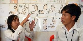 دانشجویان کامبوجی در حال استفاه از زبان اشاره برای برقراری ارتباط در کلاس درس در پنوم پن (Tang Chhin Sothy/AFP/Getty Images)