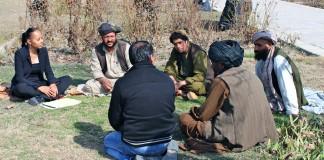 کیمبرلی ماتلی با گروهی از مردان افغان روی زمین نشسته است. (عکس اهدایی از کیمبرلی ماتلی)