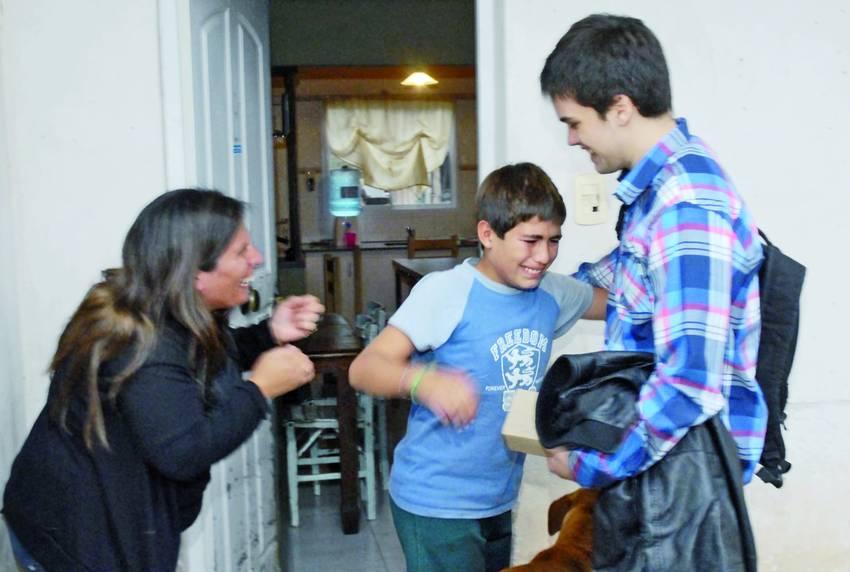 Un jeune homme apporte une prothèse de main à un enfant, qui pleure de joie, à côté de sa mère qui sourit (© Clarín)