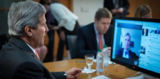 John Kerry sitting and watching a computer with Bill Nye in the background (State Dept.)