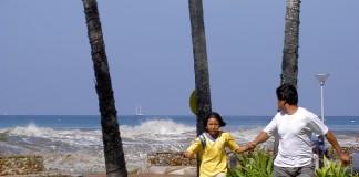 Une fille et un homme s'éloigne de la mer en courant, main dans la main (Flickr/Alan C.)