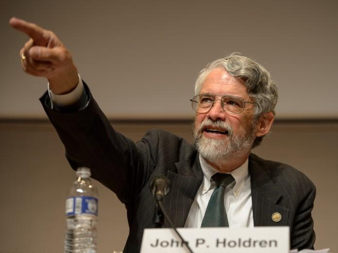 John Holdren, assis devant un microphone et pointant du doigt (NASA)