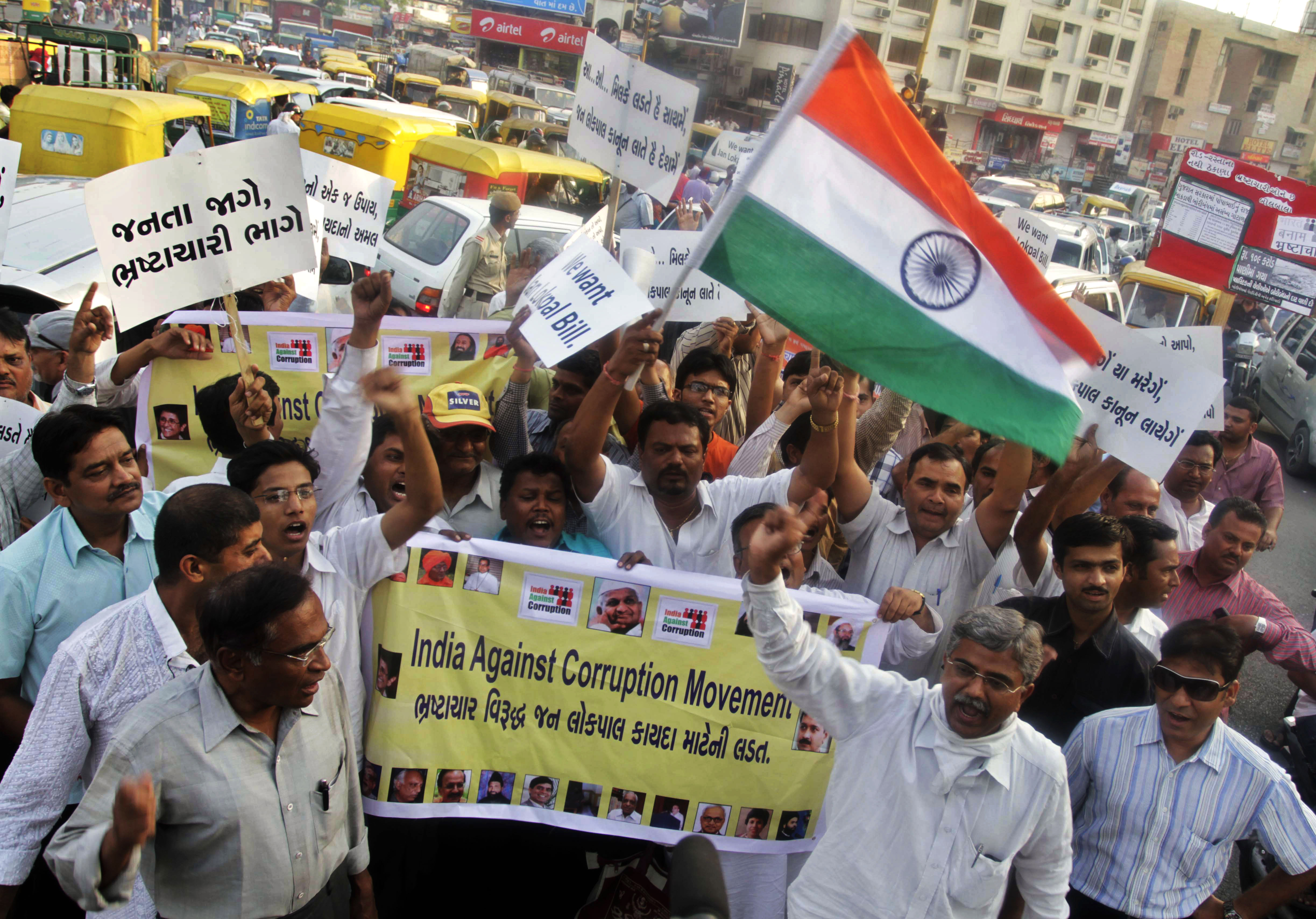 Crowd of anti-corruption campaigners marching in street (© AP Images)