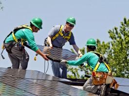 ثلاثة رجال يركبون لوحا للطاقة الشمسية على سطح أحد المنازل (AP Images)